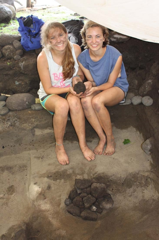 Emma Kousouris and Christine Zenel with a stone fishing weight discovered while excavating an ancient earth oven marked by fire-cracked rocks, charcoal and ash. 2012 Hanamiai excavation.