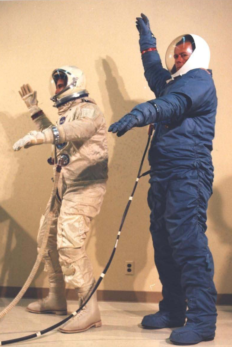 McDonnell-Douglas engineers demonstrating the reach and flexibility of the the David Clark G4C and Hamilton Standard MH-5 space suits. ( NRO MOL photograph 18 . Credit: NRO and McDonnell-Douglas).