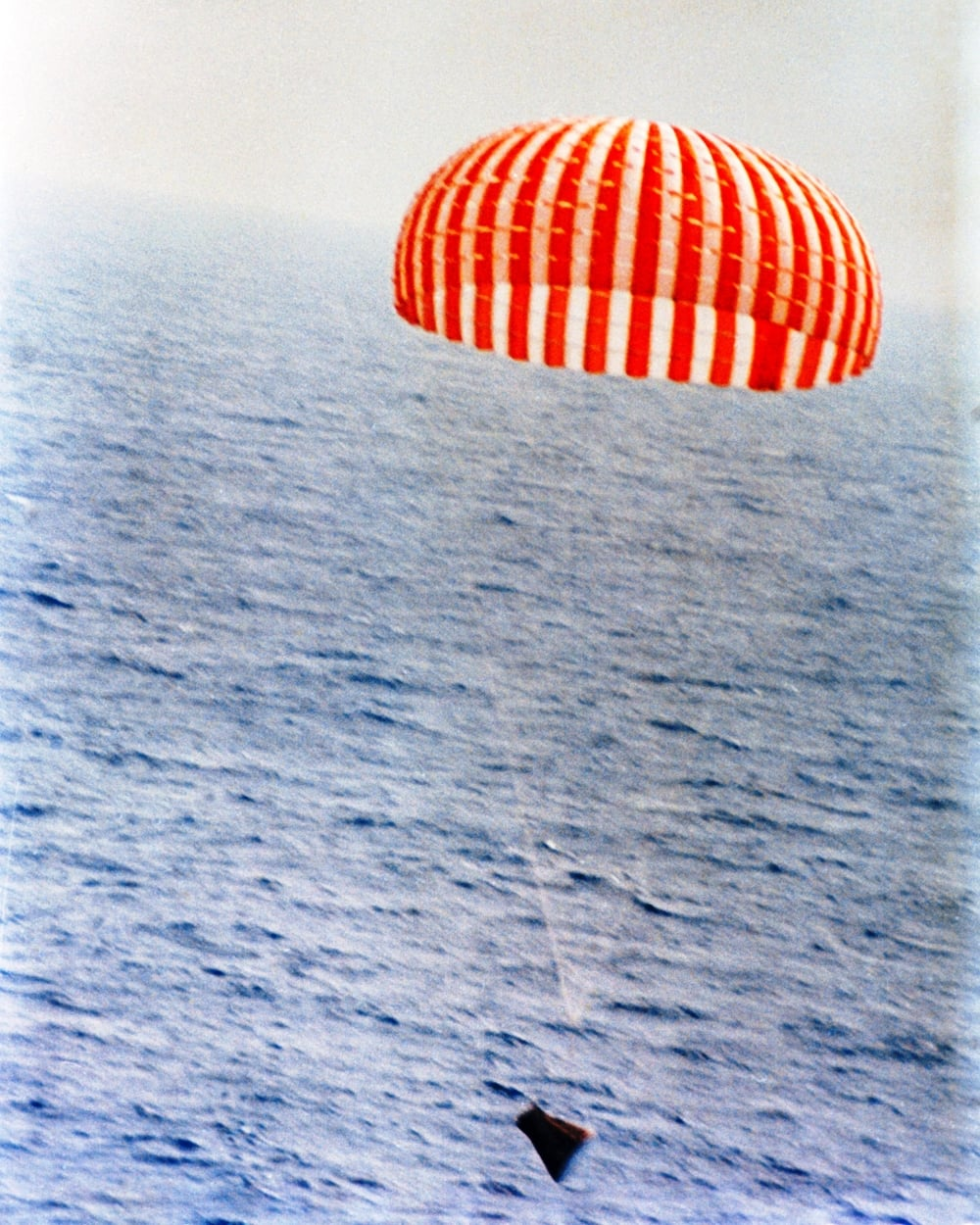 Gemini 9 nearing splashdown on June 6, 1966. Note the truncated nose and the high attach point of the parachute risers to the nearly-invisible bridle. (NASA Photo s66-34115.)