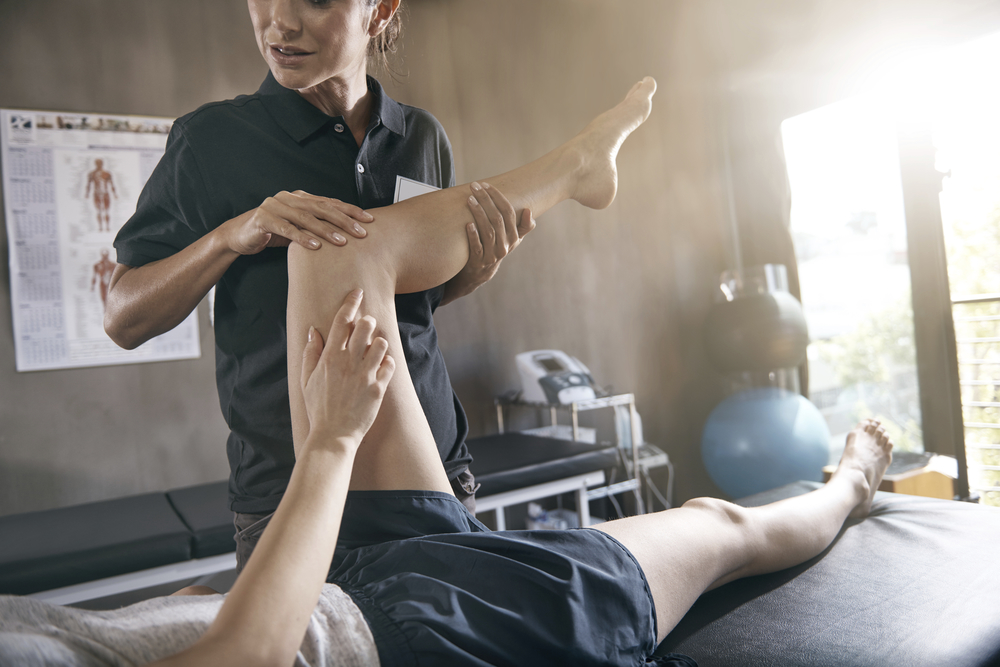 therapist lifting leg of patient