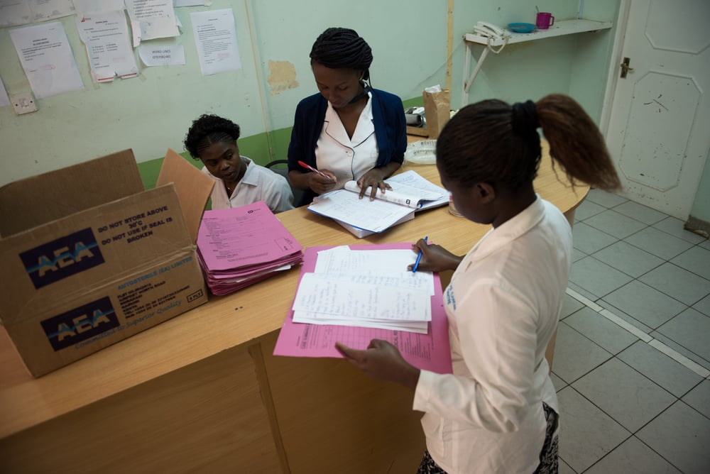 Physician's assistant, Carol Apondi, right, nurse Milca Mwankiki, center, and a medical student file patient logs at the Nurse's Station on the second floor the center. All the nurses working at the center have received specialized training in palliative care and work exclusively with patients who are terminally ill.