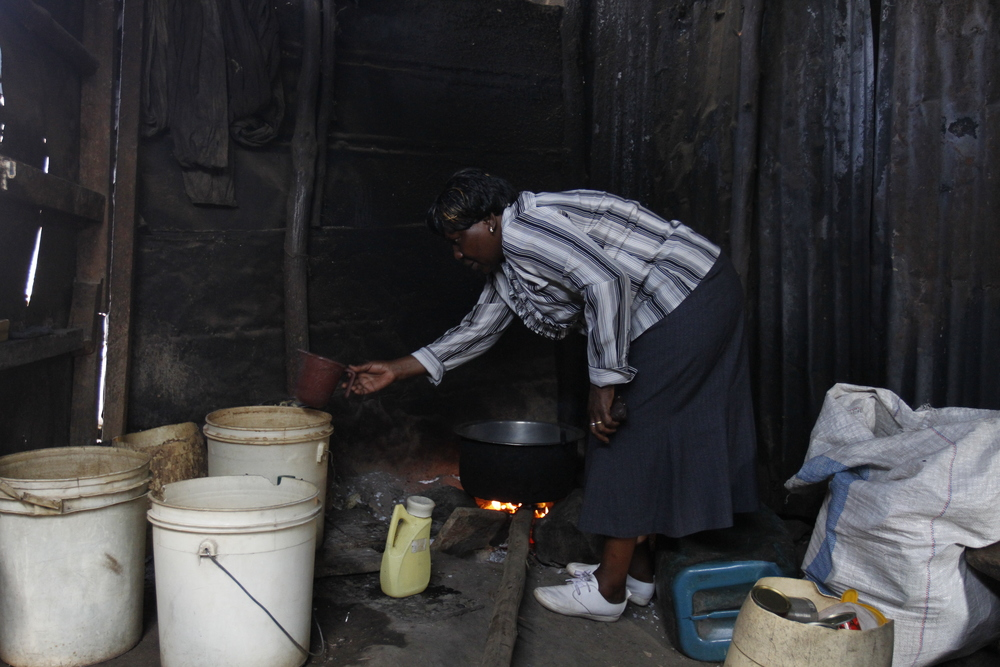 Rosemary prepares local brew for a customer at her bar in Nairobis Mathare slum where she distills and sells local brew for a living on 27th August