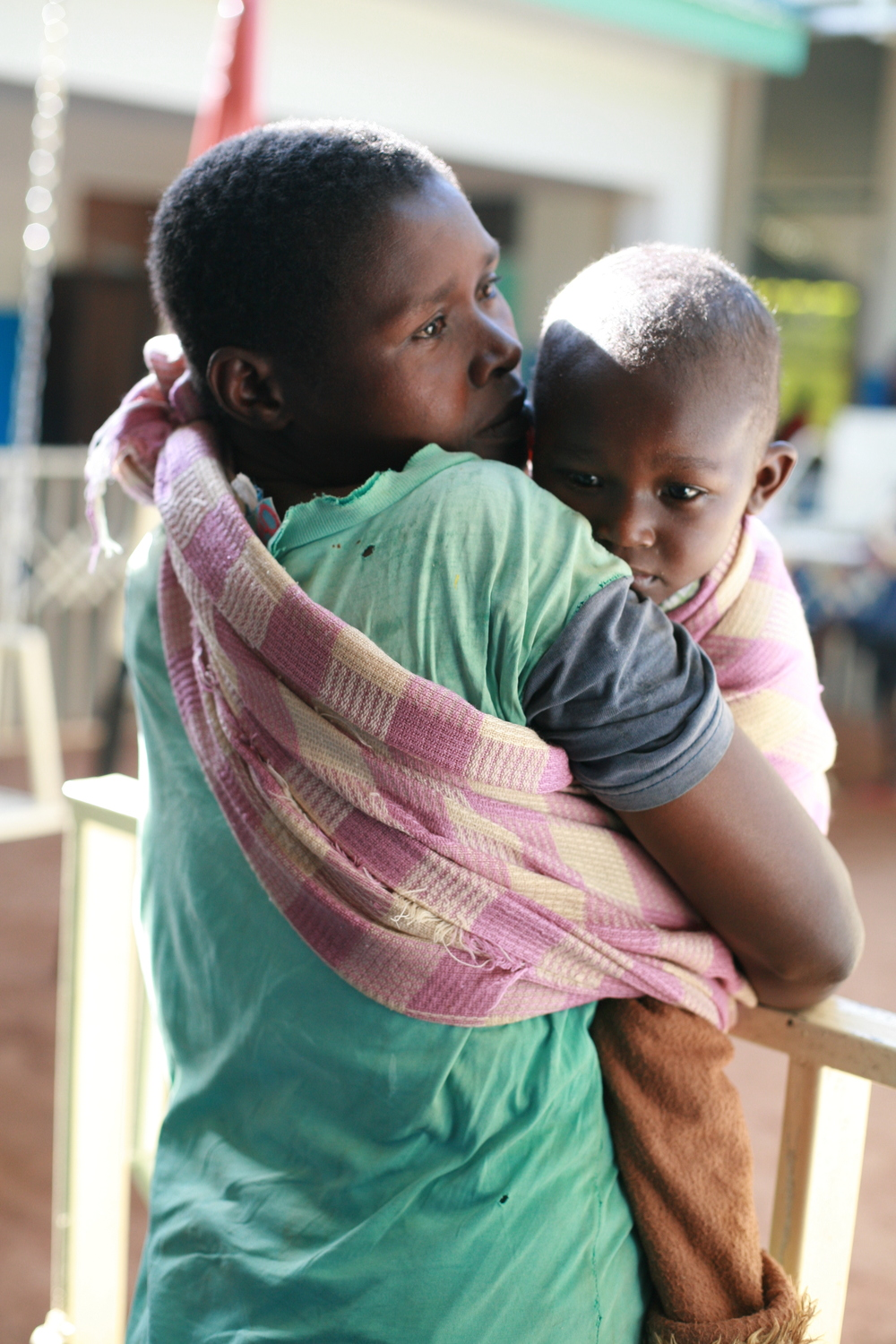 A mother comforts her son as they wait for the doctors to set up for his treatment.JPG