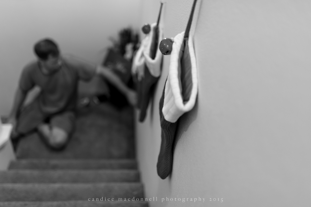 husband hanging christmas stockings on stairwell © candice macdonnell 2015
