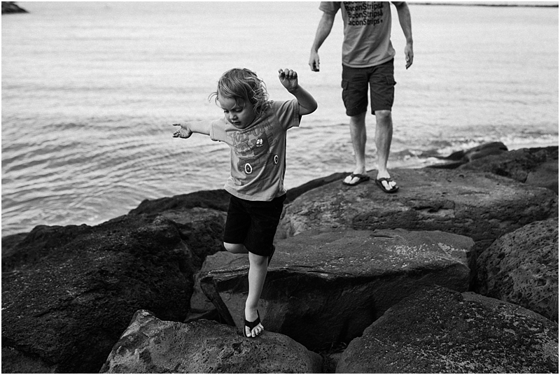 child jumping on rocks at beach lifestyle family photographer