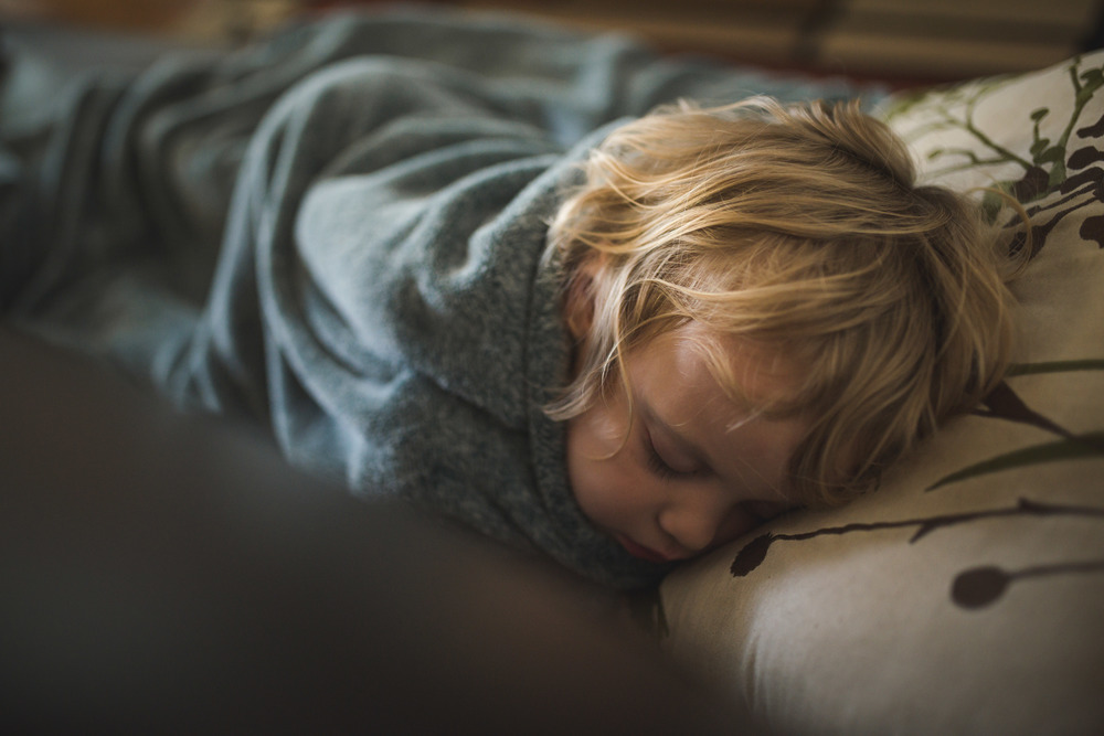 little boy sleeping on couch family photographer