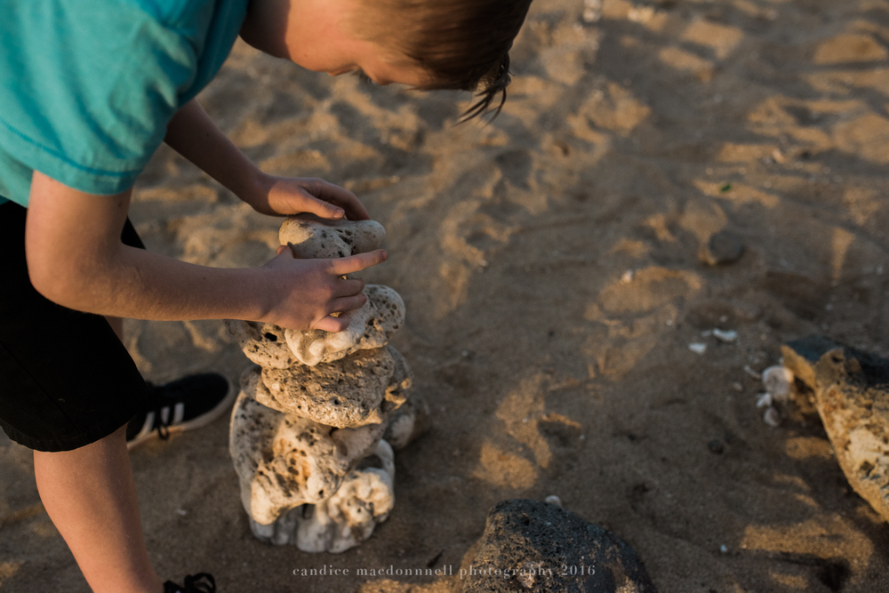 stacking stones at kaena point beach lifestyle photography by candice macdonnell photography, oahu hawaii documentary photographer