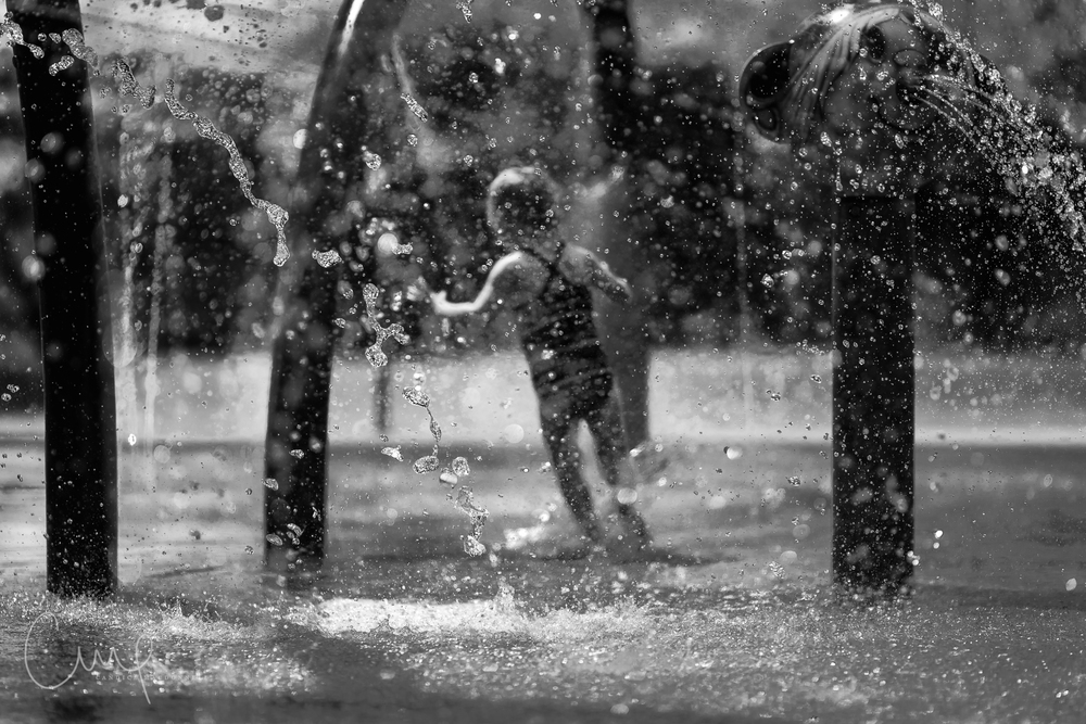 girl running in water at splash park oahu hawaii children documentary photographer