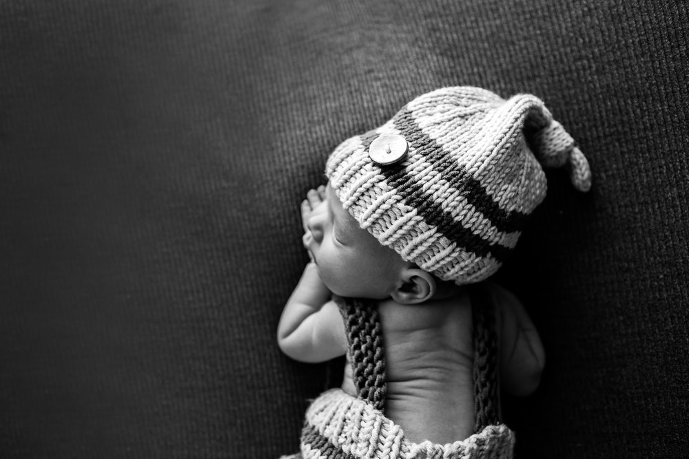 black and white newborn photograph baby wearing hat and pants