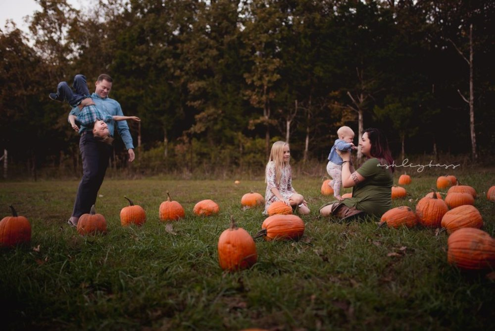 family playing at a pumpkin patch