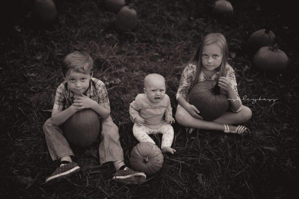 three kids sitting with pumpkins