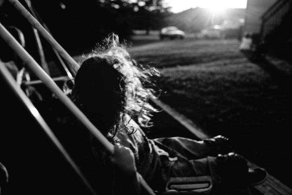 boy with long hair swinging lifestyle photography missouri