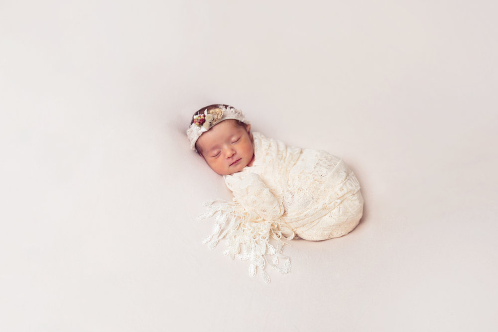 newborn baby girl on white background with lace wrap fort leonard wood newborn photographer