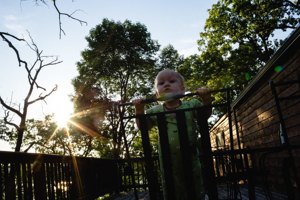 baby on porch standing on patrio chair with sunburst behind her camping documentary photographer