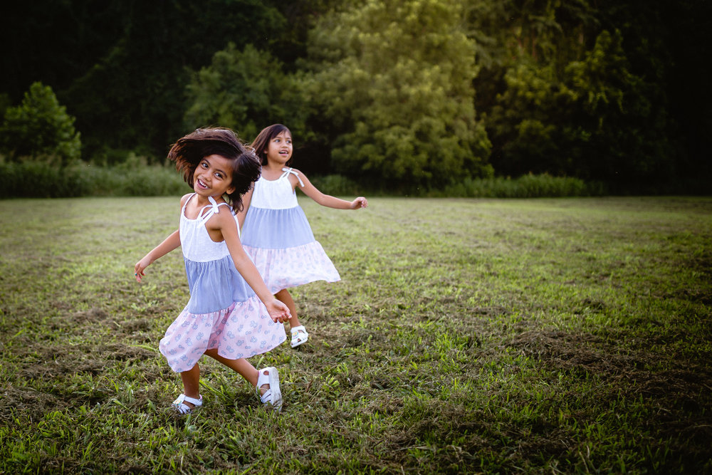 two little girls running in field lifestyle photography waynesville mo