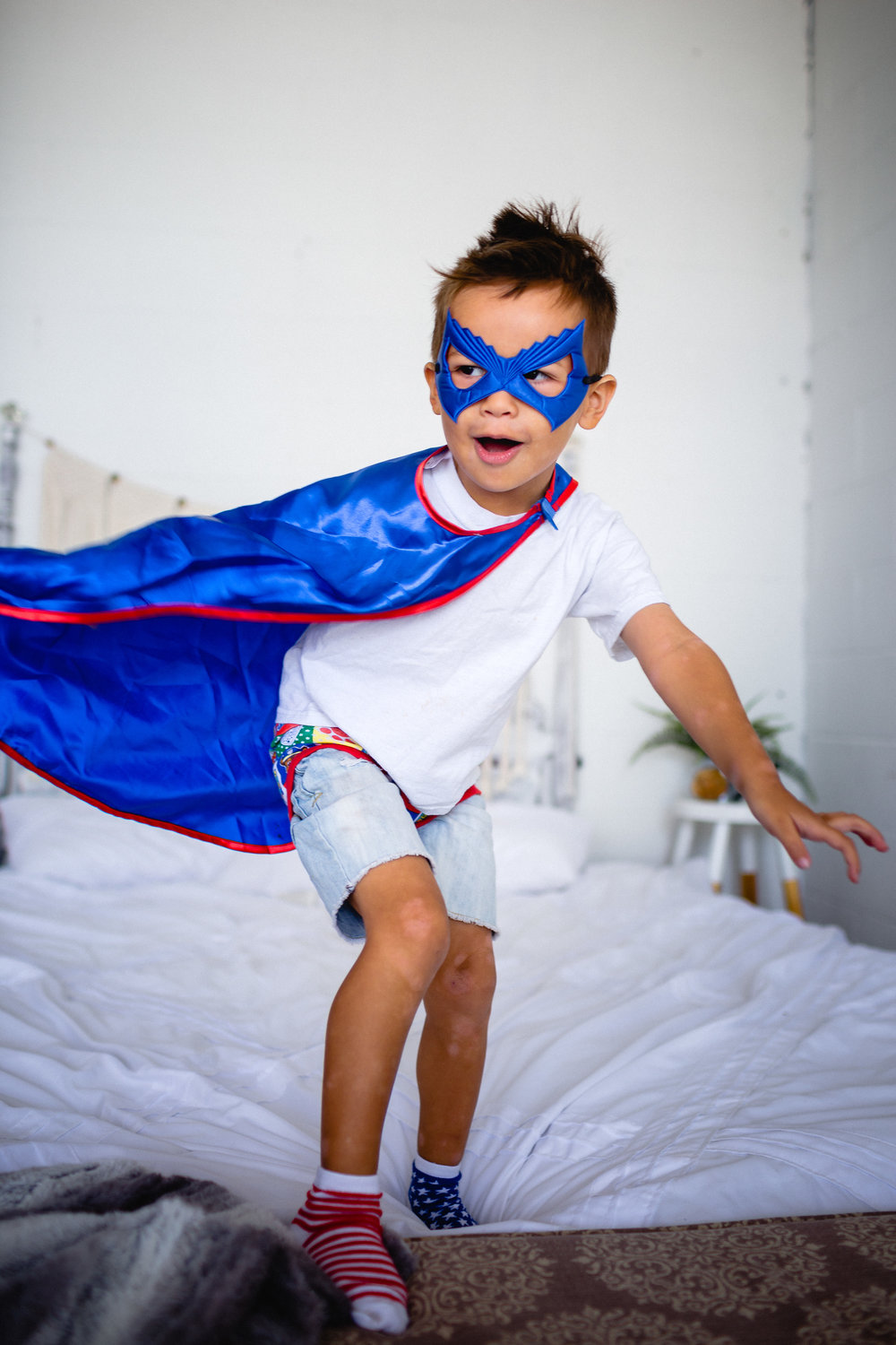 super hero kid jumping on bed lifestyle photographer waynesville