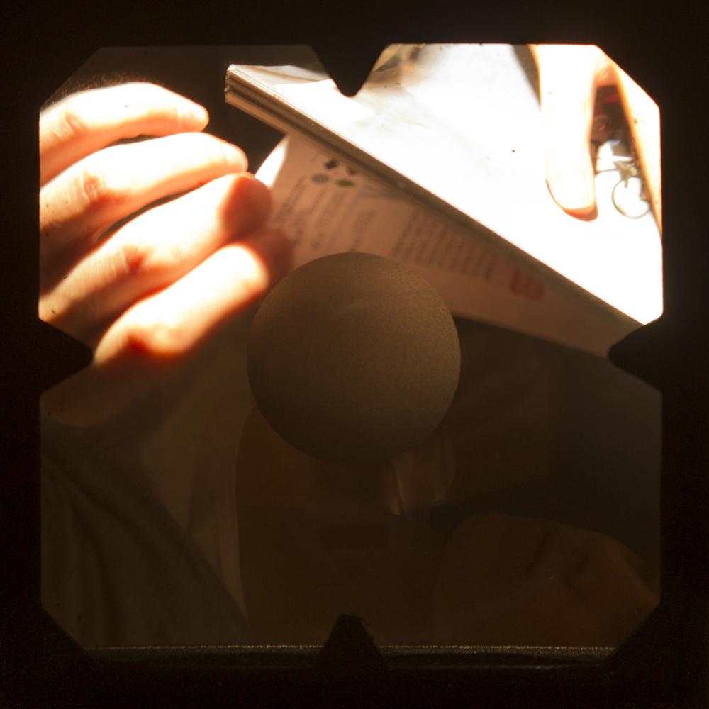 Podpis k reprodukciji:   Amadeus Birca  (4. letnik):  Ženska bere knjigo preden skoči v bazen  ,   2017  ( Woman reading a Book before jumping into the Pool ), fotografija, inkjet print na folijo, 9,7 × 9,7 cm,mentor: doc. mag. Tanja Verlak, M. Phil.