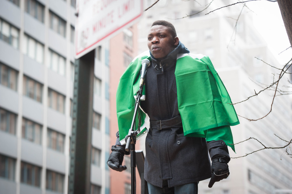 "(March 7th 2015) Activist Michael Ighodaro speaks of the trials LGBT face in Nigeria in front of the Consulate General of Nigeria during a demonstration on Nigerian Global Day of Action.""I am Nigerian by birth, just as I am gay by birth. I was born gay. And I am now American, grateful to find safety and support here but far from the home where I belong, because my own government says who I am and who I love is a crime."""