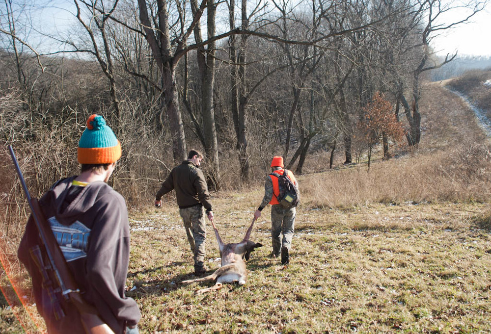 (January 5th 2012) Young hunters of Western PA drag the carcass of a deer they tracked all morning and most of the afternoon back to their property over the hill.