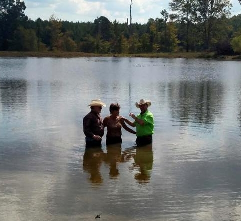 Chad White (r), pastor of the Maverick Cowboy Church of El Dorado, Arkansas conducting a baptism in a country pond