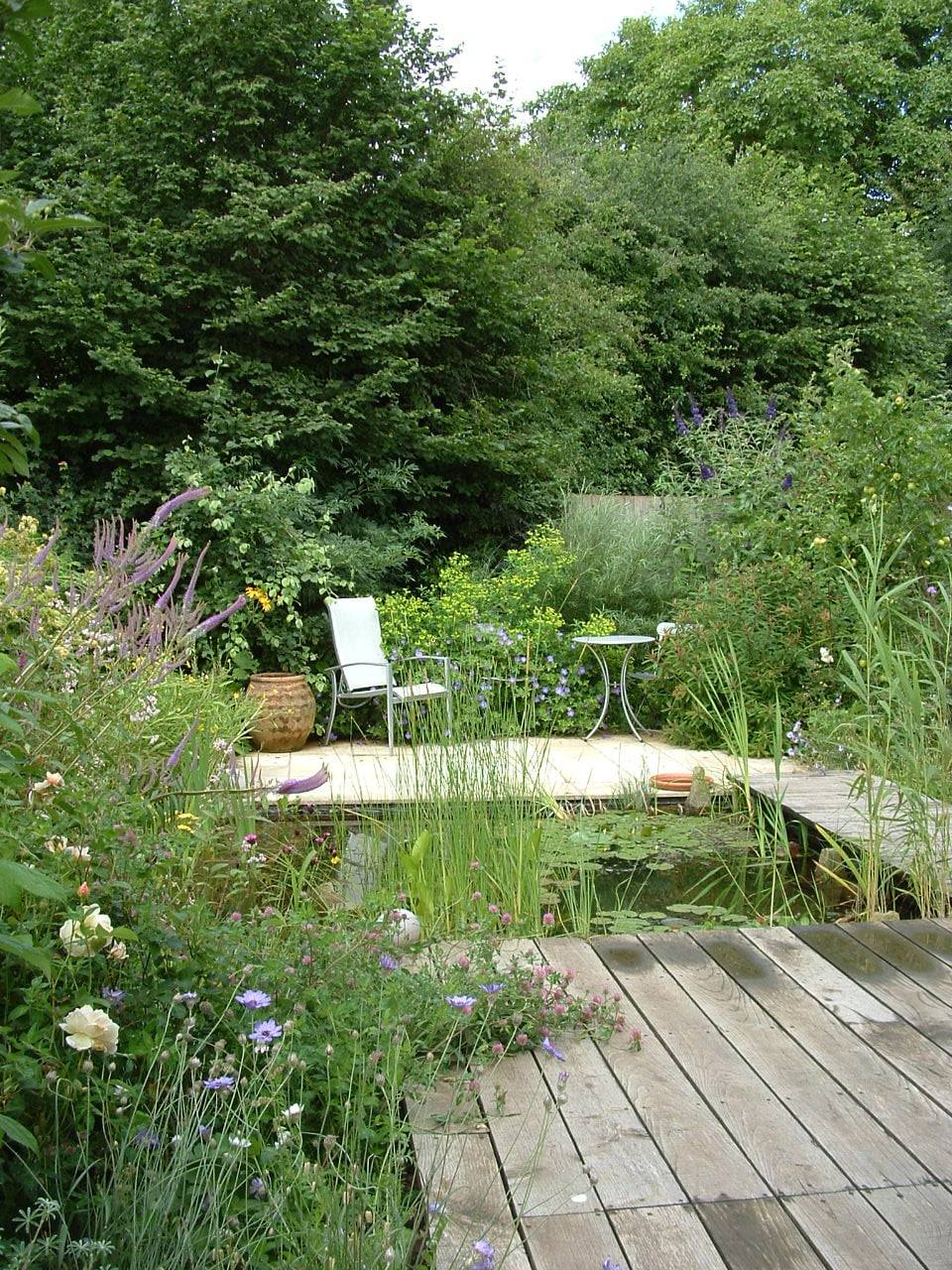 A small estate garden is transformed into an oasis for wildlife and people with lush planting, water and secluded sitting areas.