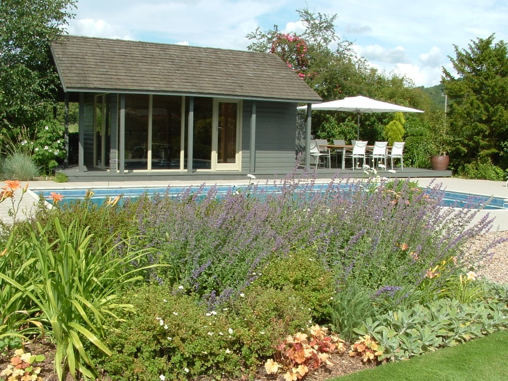 An outdoor swimming pool with a welcoming summer house and relaxing place to sit behind a summer flowering border of Nepeta, Potentilla, Hemerocallis, Heuchera  and Stachys byzantina.