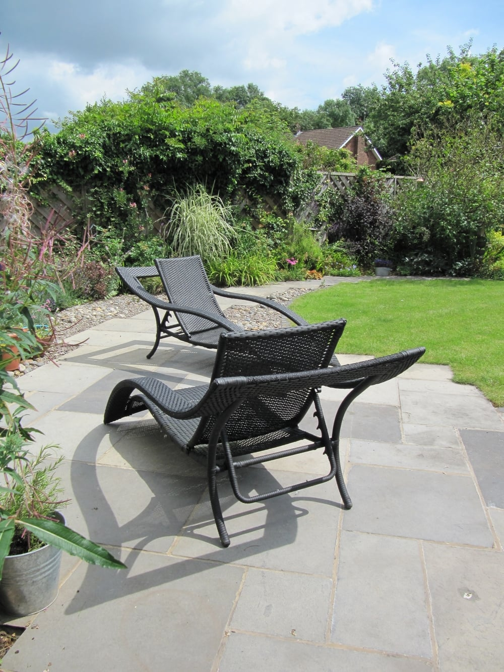 Shapely garden furniture offers a place for relaxation in a sunny suburban Cardiff garden.
