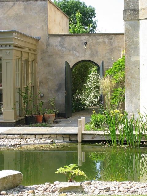 A large garden pond through inviting entrance gates.