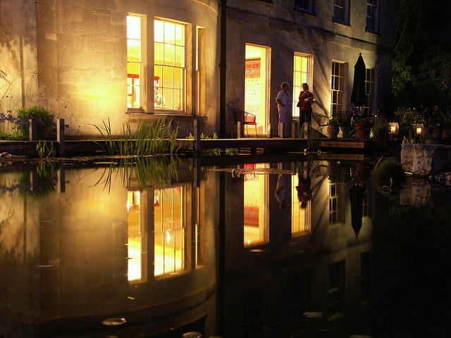 At night the lights from the windows of this lovely regency home are reflected in the pool giving an exciting dimension to this Gloucestershire garden.