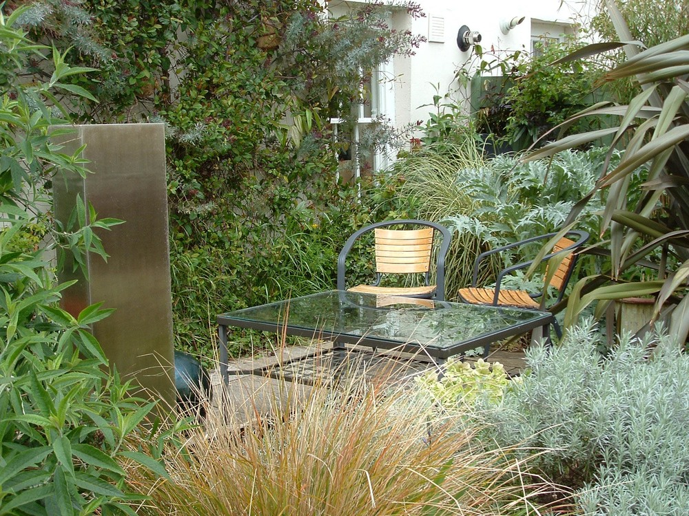 This design for a small mews courtyard garden makes space for a steel water feature by placing the table over the formal pool.