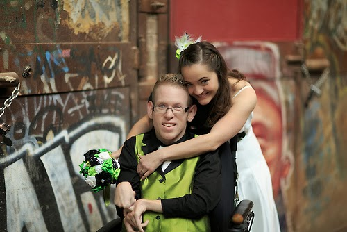Young man in wheelchair, woman standing behind him, hugging him, both facing the camera and dressed for wedding.