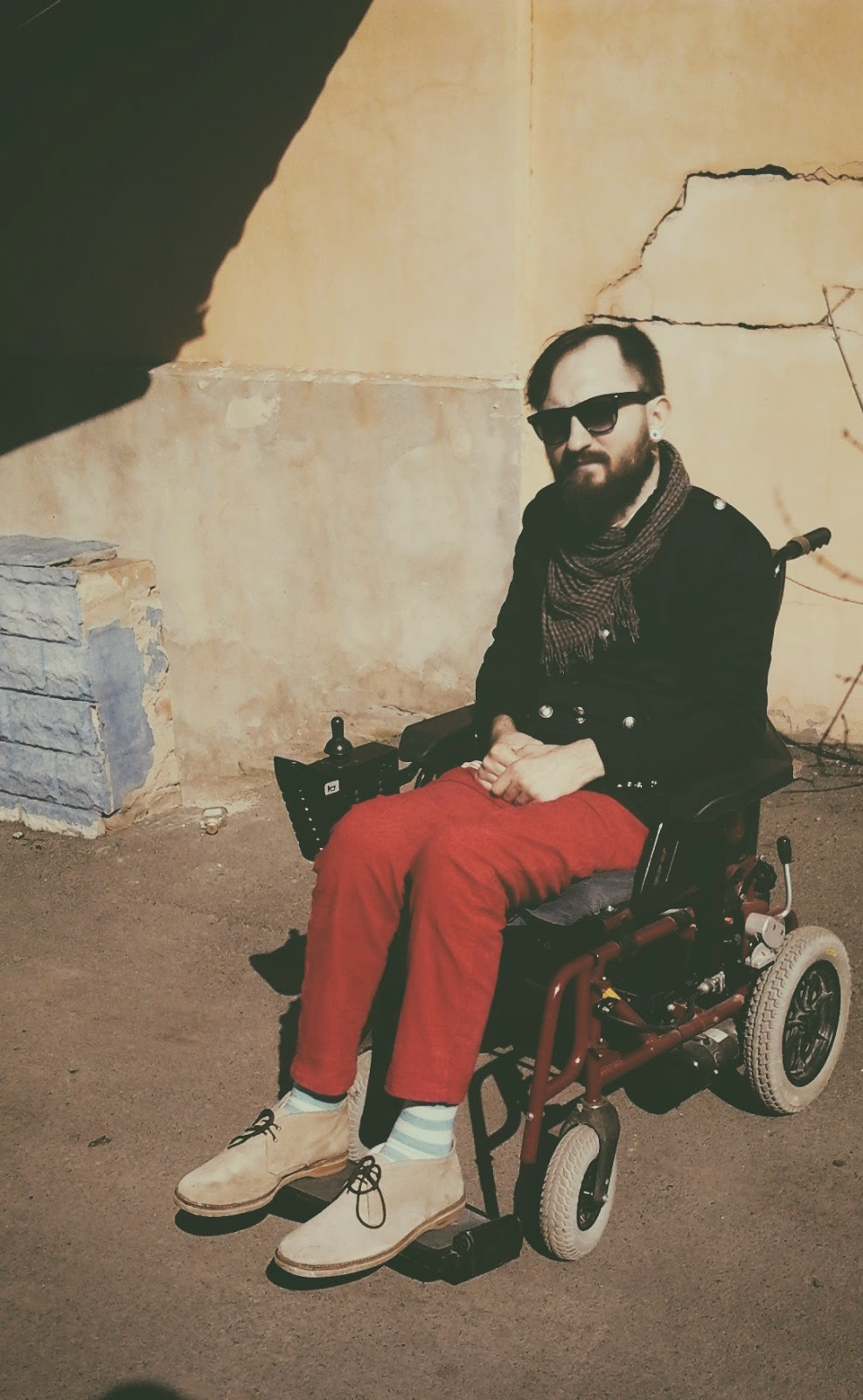 Man with full beard and mustache, wearing sunglasses, sitting in an electric wheelchair. Wearing bright red pants and a dark jacket