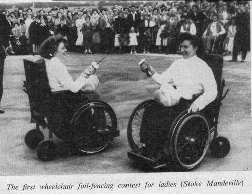 black and white photo of two women in wheelchairs fencing, in front of a standing audience