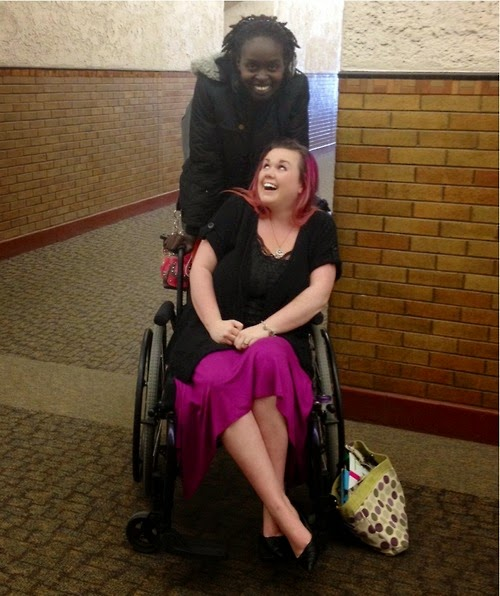 Young white woman with pink highlighted hair sitting in a manual wheelchair, looking up at an African-American woman standing behind the chair, holding the push handles