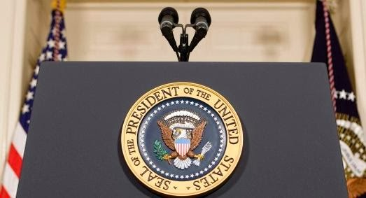 Close-up photo of Presidential speaking podium with two microphones and the seal of the President