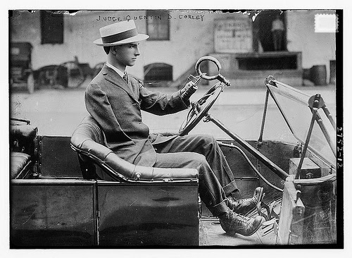 1920s black and white photo of a man driving a car with prosthetic arms.
