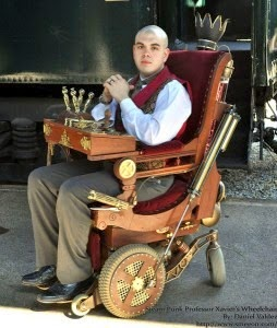 "Man with shaved head sitting in a customized ""steampunk"" wheelchair"