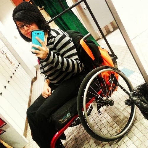 Photo of an Asian young woman wearing glasses, a black and white striped shirt, sitting in a wheelchair, taking selfie with a smartphone