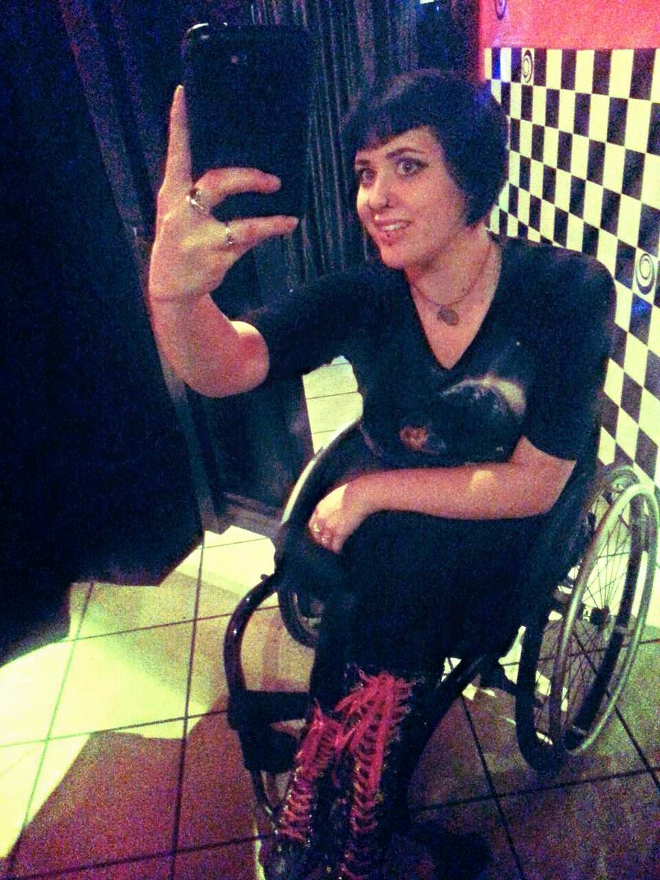 Woman with short black hair, wearing dark patterned clothes and tall boots with red laces, sitting in a a wheelchair, with hand up holding iPhone