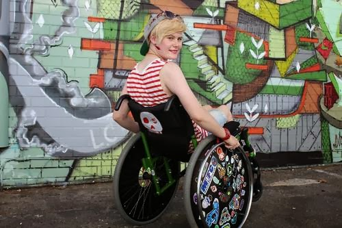 Young woman with blonde, short hair, wearing sunglasses up on her head, in a wheelchair decorated with myriad stickers, in front of a graffiti-covered outdoor wall.