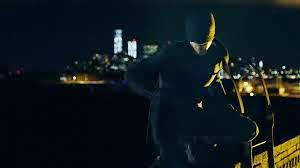 Photo of Daredevil character, in black suit with mask over most of face, in front of nighttime NYC skyline
