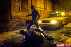 Screen shot of Daredevil in action, at night, with police car nearby, man beaten on the ground at his feet