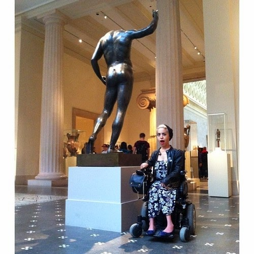 Blonde woman in an electric wheelchair, wearing floral printed dress, looking surprised, next to bronze statue of a man, without head in a museum atrium