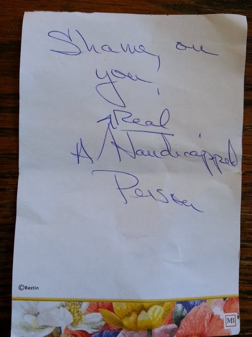 "Handwritten message on personal notepaper reads ""Shame on you! A Real Handicapped Person"""