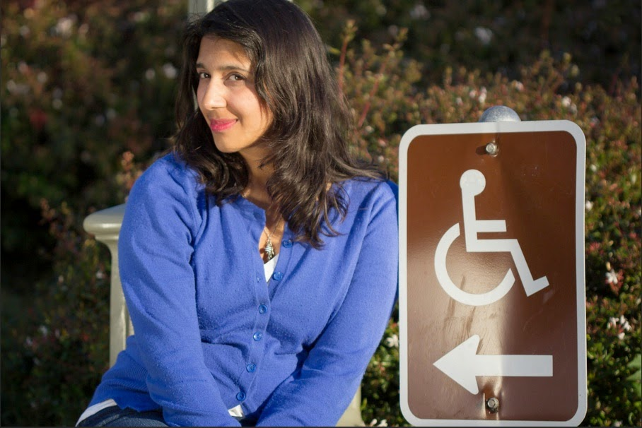 Young woman with long black hair sitting next to a handicapped parking sign with an arrow pointing in her direction