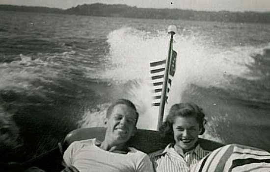Black and white photo of young man and young woman seated next to each other in the back seat of a running motorboat