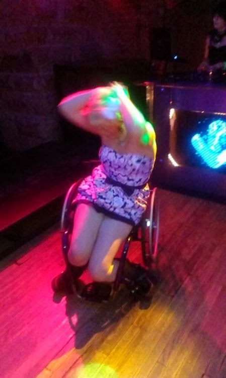 Blonde woman in wheelchair making dance moves, with colored club lights and blurred movement