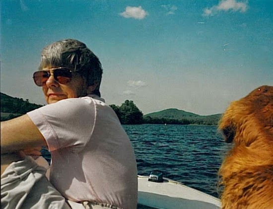 Adult woman in sunglasses, sitting in a motorboat on the water, with golden retriever next to her