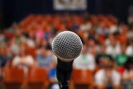 Closeup photo of a microphone with an audience in the background, slightly out of focus