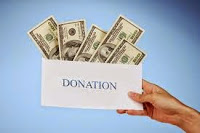 "Photo of a hand holding an envelope labeled ""DONATION"", stuffed with dollar bills"